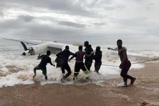 عکس/ بیرون کشیدن لاشه هواپیما توسط مردم بومی